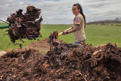 female turning compost pile with pitchfork