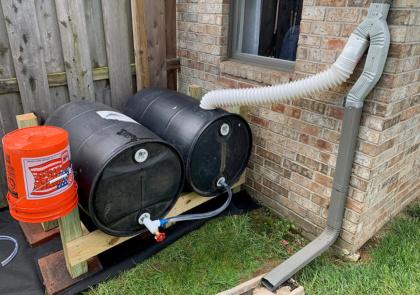 two horizontal rain barrels next to a house