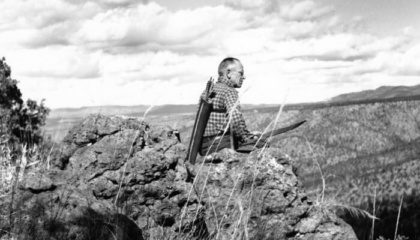 black and white photo of aldo leopold sitting on a rock cliff